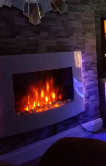 white wall mounted electric fire with pebbles and LEDs